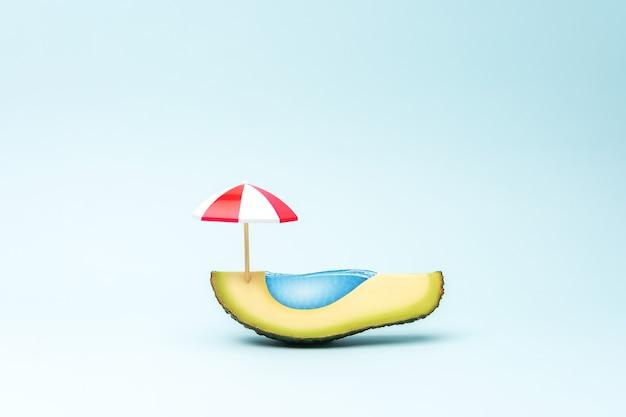 Бассейн из фруктов авокадо и зонтик от солнца
