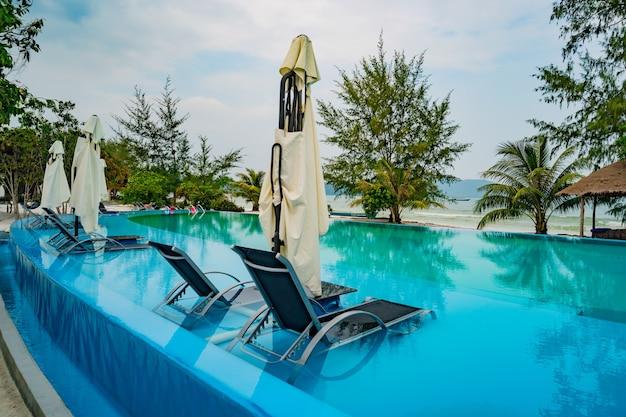 豪華なホリデーホテルのスイミングプール、素晴らしい景色。トロピカルリゾートで観光客を待っている手すり、サンベッド、サンラウンジャー、パラソルのあるプールの近くでリラックスしてください。水中のデッキチェア