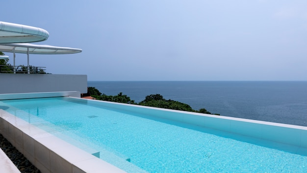 Swimming pool overlooking view andaman sea and clear sky background,summer holiday background concept.