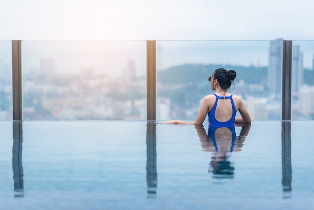 Swimming pool on roof top with beautiful city and sea view, asian travel and vacation