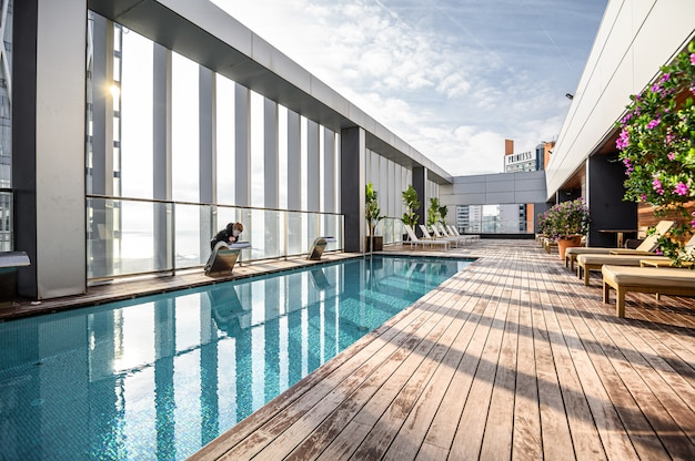 Swimming pool on roof top with beautiful city view of the skyscrapers. . premium hotel. 03.01.2020 barcelona, spain