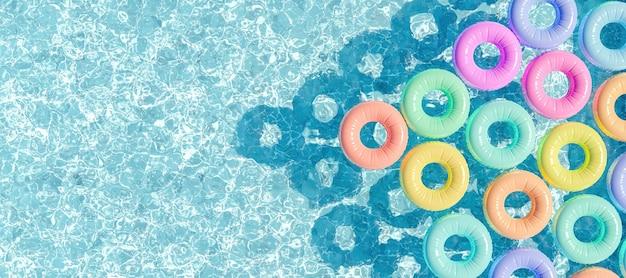 パステルカラーに浮かぶリングがたくさんある上から見たプール