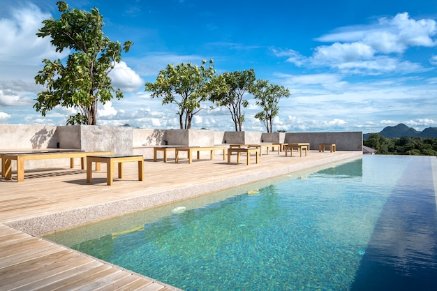 Swimming pool on top of roof deck building and sunny reflections with teak wood flooring stripes summer vacation