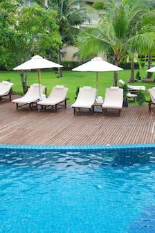 코코넛 나무와 하얀 우산 수영장
