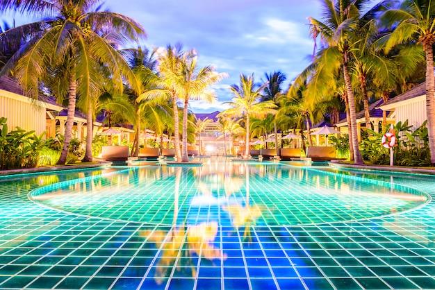 Бассейн с пальмами в курортном отеле ночью