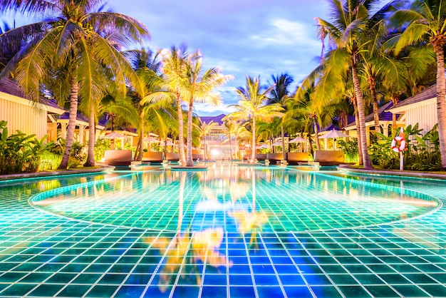 Swimming pool with palm trees in resort hotel at night