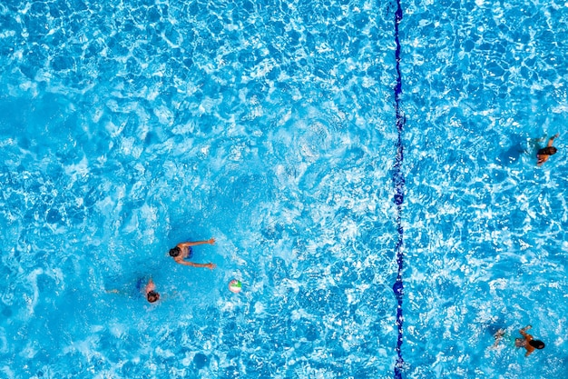 Swimming pool with playing people, overhead view