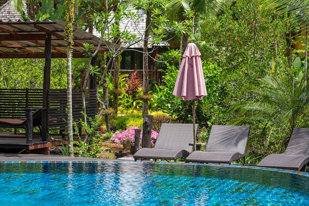Swimming pool with relaxing beds and sun umbrella in tropical garden near beach in thailand