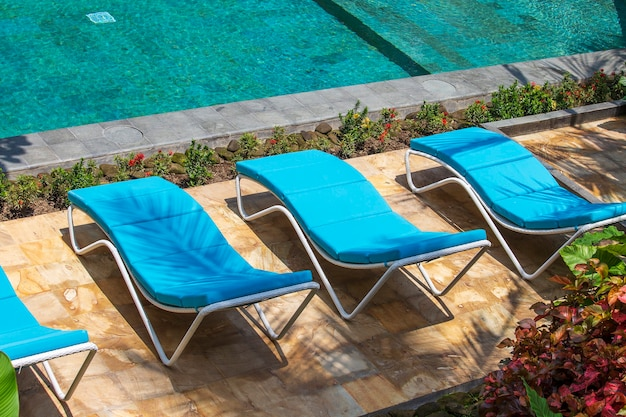 Swimming pool with relaxing sun beds in tropical garden in island bali, indonesia