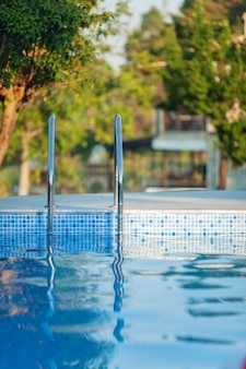 Swimming pool with a shiny railing and a sunny day