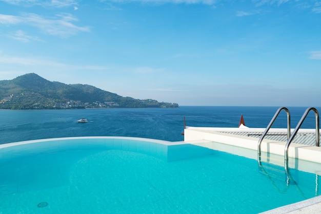 보기 열대 바다를보고 지붕 갑판 건물 위에 계단이있는 수영장