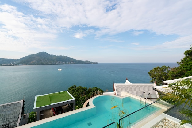 Swimming pool with stair on top of roof deck building looking at view tropical sea ,luxury beach villa house with sea view swimming pool in modern design,summer vacation and travel background concept.