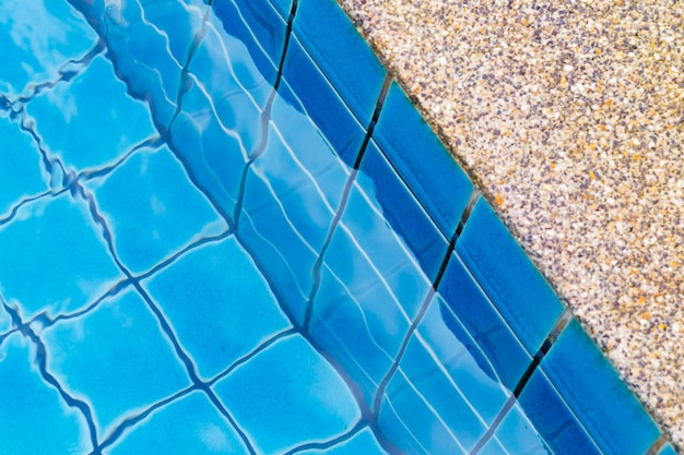 Swimming pool with a stone flooring beside it