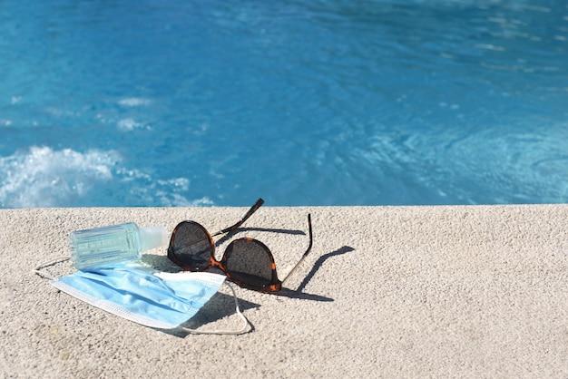 サングラスと保護マスク付きのスイミングプール