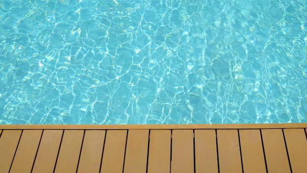 Swimming pool with wooden deck in summer time.