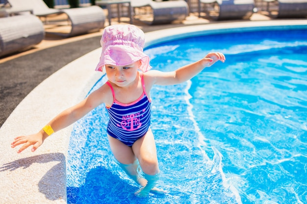 Swimming, summer vacation - lovely smiling girl in pink hat and blue swimsuit playing in blue water in a pool.