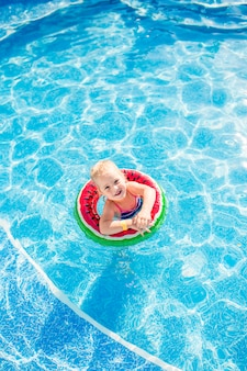 Swimming, summer vacation - lovely smiling girl playing in blue water with lifebuoy-watermelon.