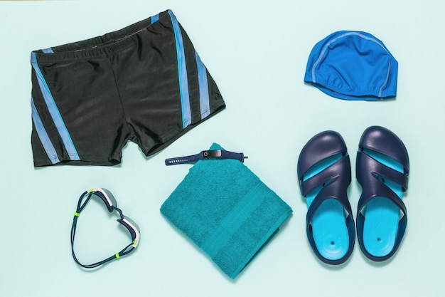 Swimming trunks, slates, swimming glasses and a towel. accessories for swimming in the pool. flat lay.