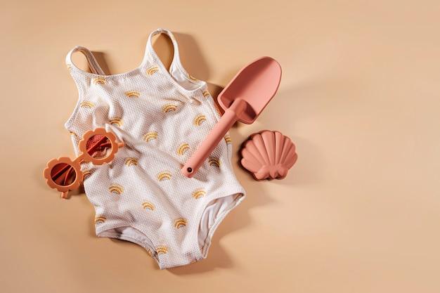 ビーチおもちゃの水着とサングラス。子供のためのビーチサマーアクセサリーの上面図。休暇のためのモダンなセット。フラットレイ