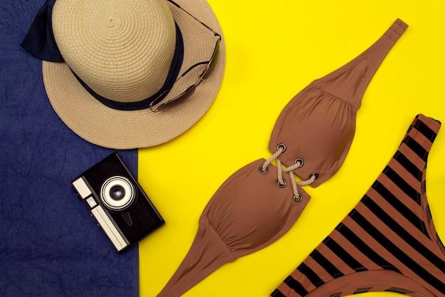 水着、サングラス、帽子、黄青色の背景にカメラ