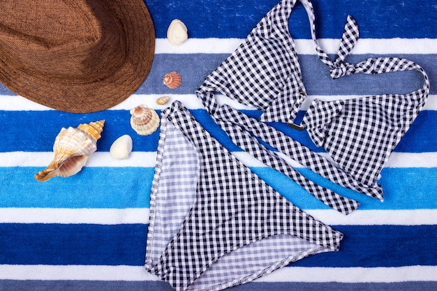 Swimsuit with beach accessories on blue towel