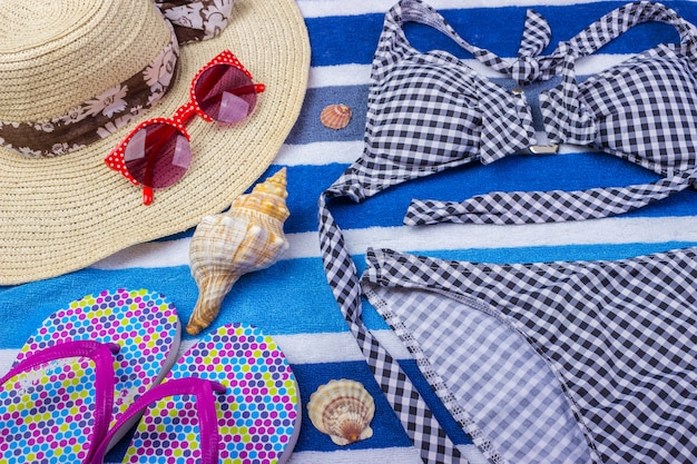 Swimsuit with beach accessories on blue
