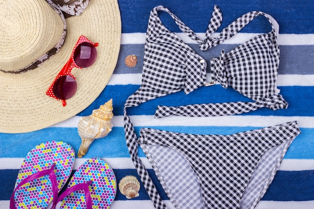 Swimsuit with beach accessories. sun glasses top view seashell shorts flip flops swimsuit