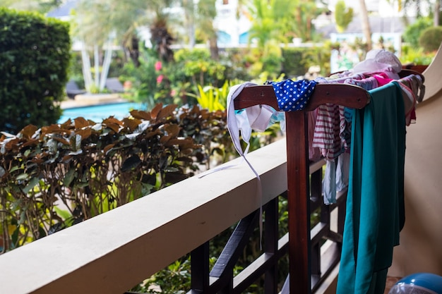 열대 정원을 배경으로 발코니에서 수영복과 비치 타월을 말리고 있습니다.