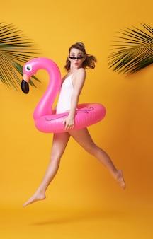 Счастливый прыгать молодой женщины одетый в swimwear держа фламинго резиновый звенит пляж.