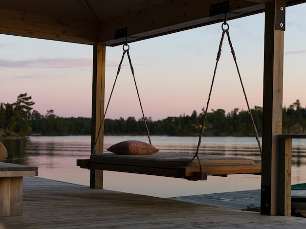 Swing chair on a dock at sunset, lake of the woods, ontario, canada