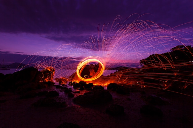 Swing fire swirl steel wool light photography over the stone with reflex in the water beautiful light in the sunrise or sunset time, long exposure speed motion style