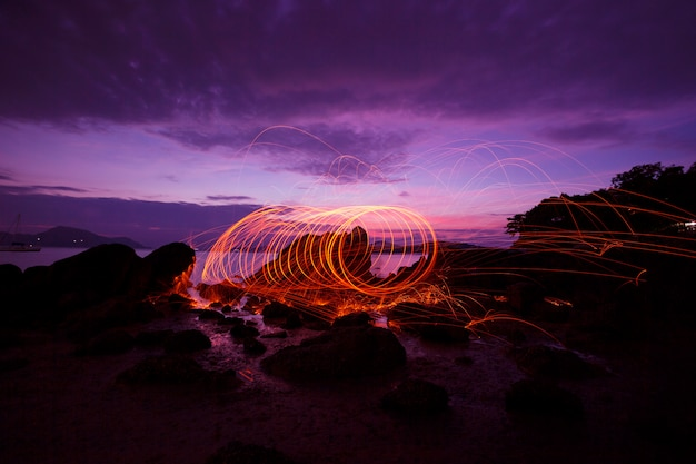 Swing fire swirl steel wool light photography over the stone with reflex in the water