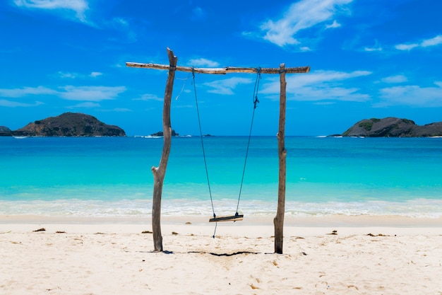 Swing made of logs on a beach of clear sand with crystal clear water on a sunny day summer travel
