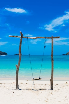 Swing made of logs on an idyllic beach on a sunny day with a blue sky summer travel vertical