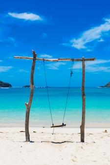 青い空の夏の旅行垂直で晴れた日に牧歌的なビーチで丸太で作られたブランコ