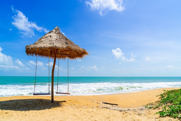 Качели на пляже с океаном, морем и фоном голубого неба