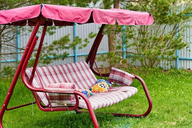 Качели розовая скамейка с навесом на зеленой лужайке в саду