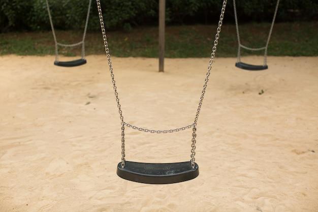놀이터에서 금속 체인에 매달려있는 스윙 세트 좌석