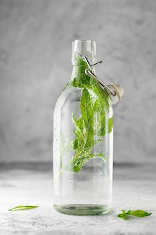 Swing top glass bottle with cold water with fresh mint leaves on grey concrete.