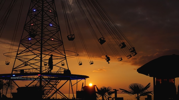 Swinging carousel roundabout chain ride at sunset. entertainment on the beach, silhouettes of palm trees on a background of sea sunset