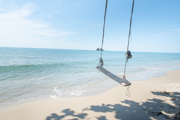 Swings on palm tropical beach,relaxing in paradise.