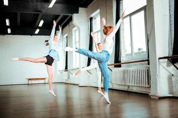Качели. рыжая учительница танцев в синих джинсах и ее симпатичные ученицы делают качели ногами