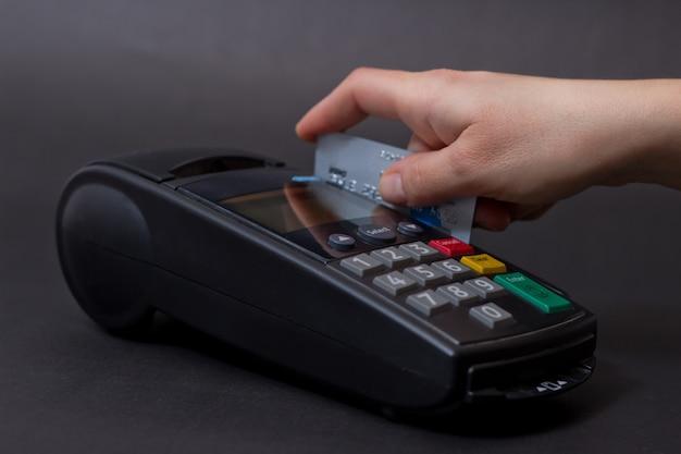 Рука swiping кредитной карты в магазине. женщины руки с кредитной карты и банковский терминал. цветное изображение pos и кредитных карт.