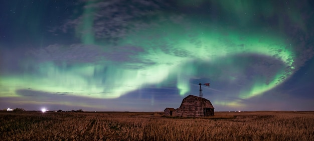 Swirl of bright northern lights over vintage barn, bins, windmill and stubble in saskatchewan, canada