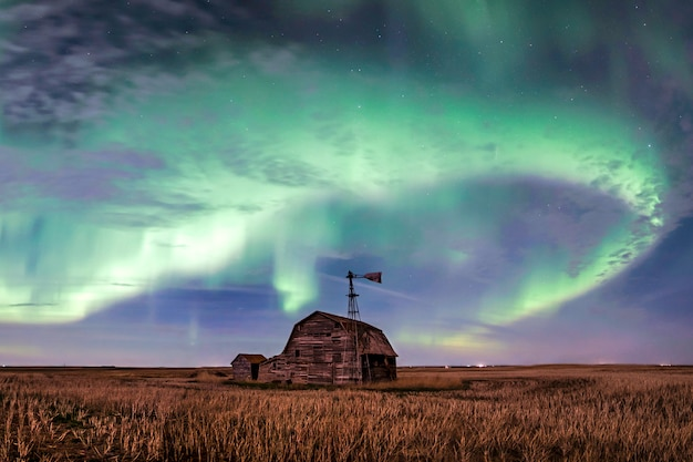 Swirl of bright northern lights over vintage barn, bins, windmill and stubble in saskatchewan, canada