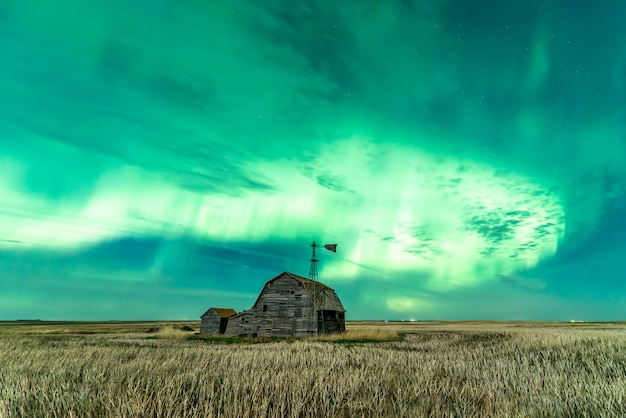 Swirl of bright northern lights over vintage barn  bins  and windmill