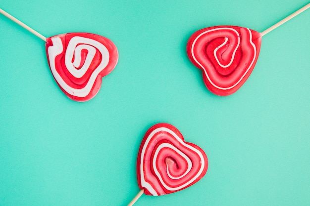 Swirl heart shape red lollipops on green background