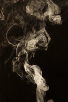 검은 배경 위에 흰색 연기의 소용돌이 운동
