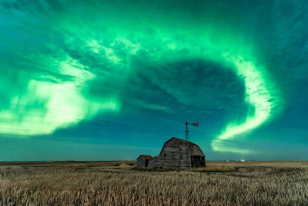 ビンテージ納屋の大箱と風車の上の明るいオーロラの渦