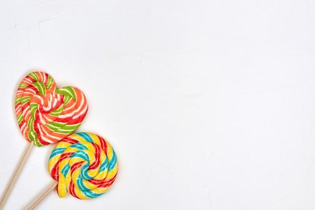 Swirl rainbow lollipop candy on white surface